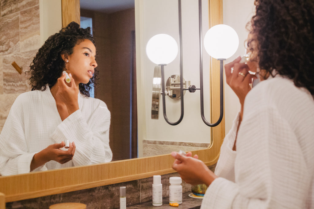 Woman applying Sagely Naturals CBD Roll-on in hotel bathroom