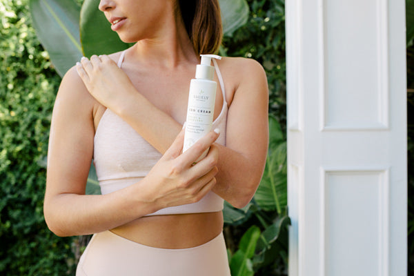 A woman wearing exercise clothing outside in front of some greenery and a white door holding a bottle of Sagely Naturals Relief & Recovery CBD Cream.