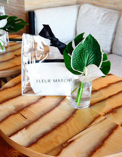The Fleur Marche Sampler Kit sitting on a wooden table behind a plant in a vase.