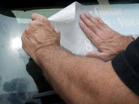 smoothing out carrier paper as it is put back down on the window glass