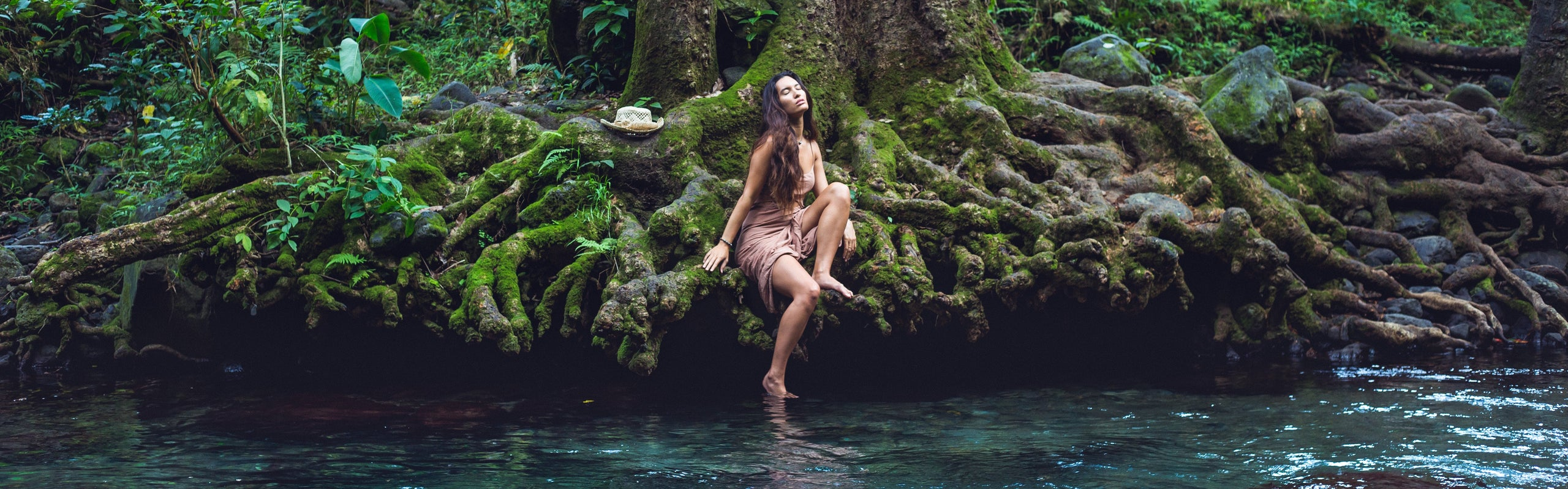 Women about to step into a flowing stream in Hawaii. She looks about to embark on a self-care routine.