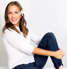 woman in white shirt and jeans sitting up with a Hawaiian flower behind her ear.