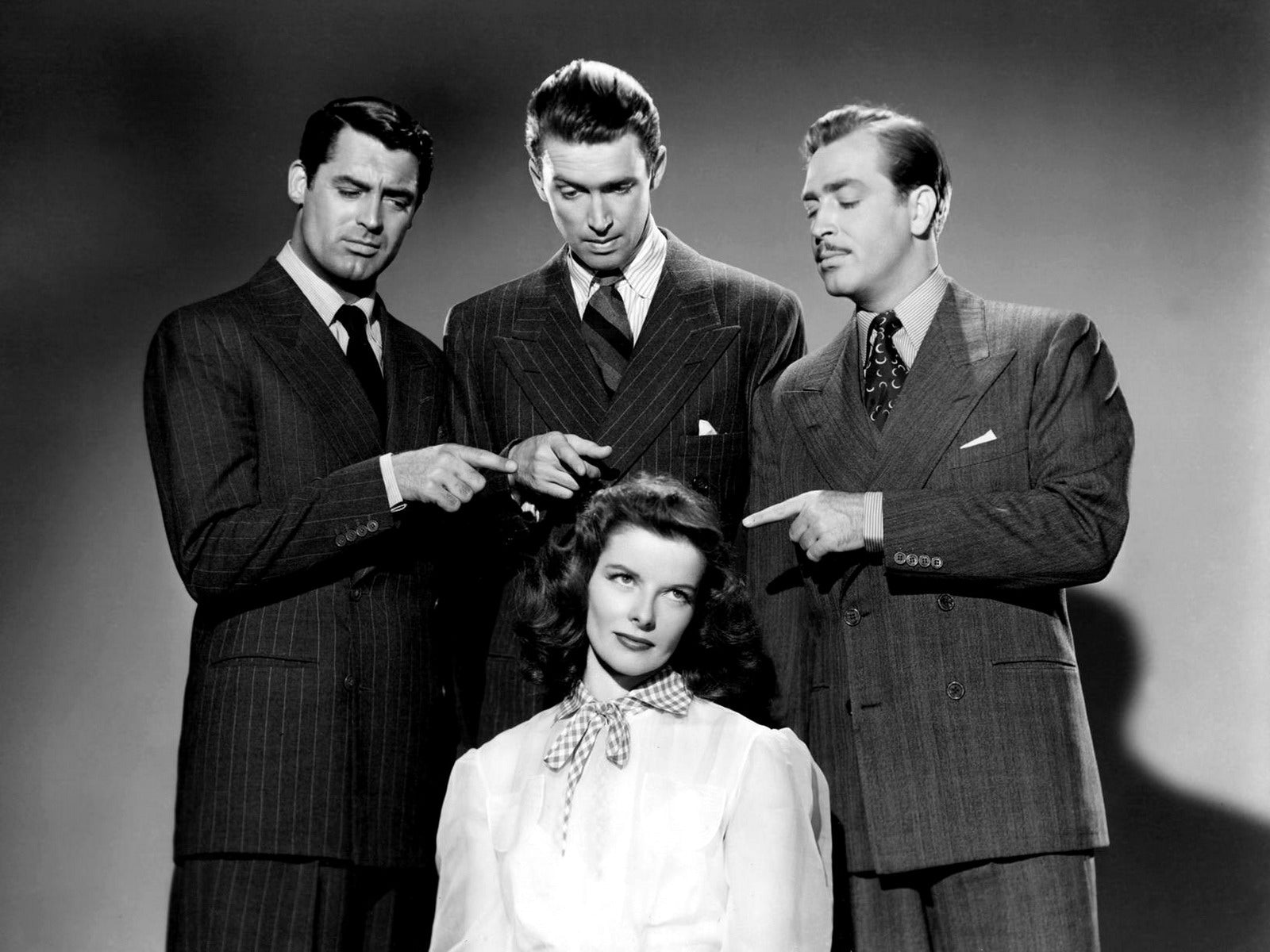 Pictured here from the movie The Philadelphia Story is Cary Grant and James Stewart in Double Breasted Pinstripe Suits along side John Howard with Katherine Hepburn in the centre. Photo Credit: The Fashionisto