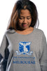 Cropped image of Female model front facing wearing Grey French Terry Dolman with large university logo
