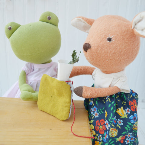 Ella Toad and Phoebe Fawn funneling the herbs into the pillow