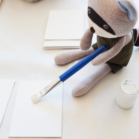 Max Racoon paints a canvas with gesso