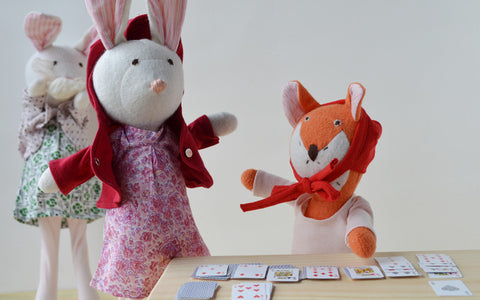 Flora Fox playing cards near Penelope and Emma Rabbit