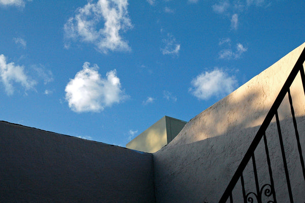 """Blue Sky"" ~ Looking up at the side of an adobe house at bright blue sky with white clouds."