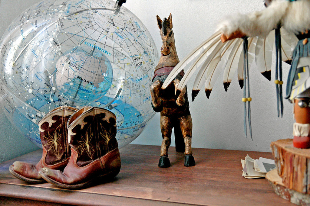"""Boots"" ~ Still life of little cowboy boots, a light globe, wooden horse and a kachina doll."