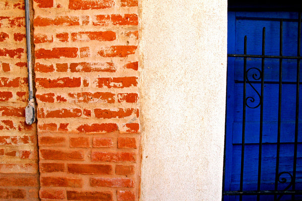"""Brick n Iron"" ~ Close up of orange brick and light pink adobe wall with a dark blue door."