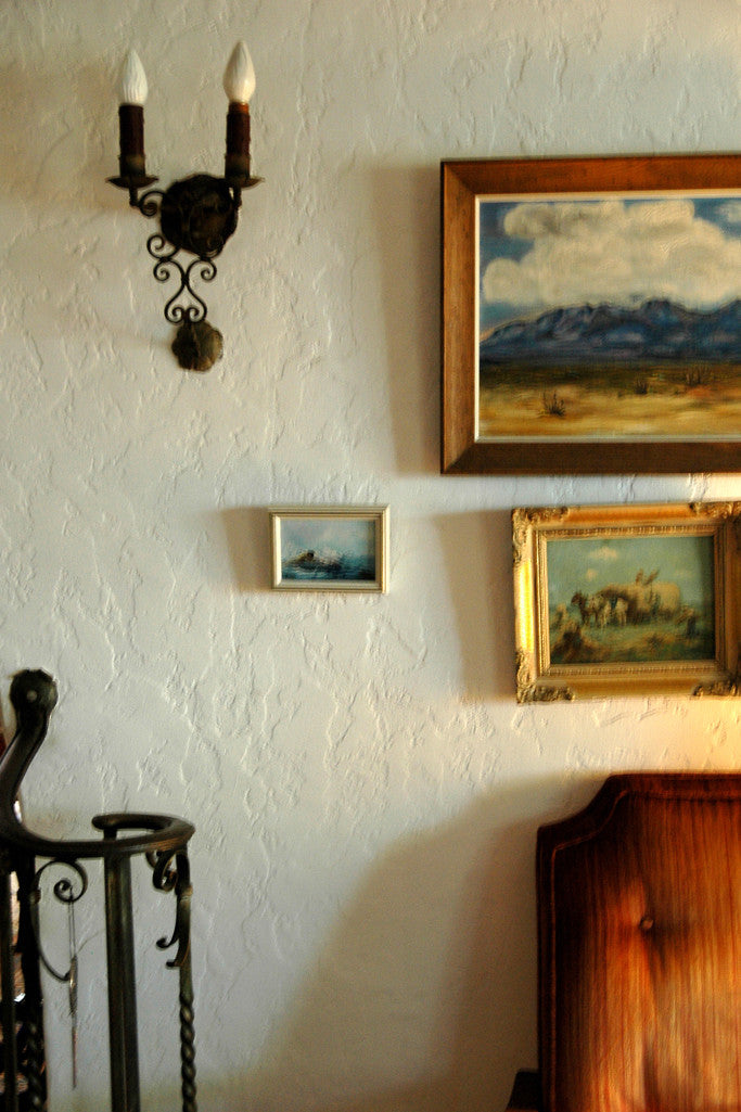 """El Paso Sky"" ~ A section of a living room with paintings and a wall sconce. Photo by Ann Woodall"