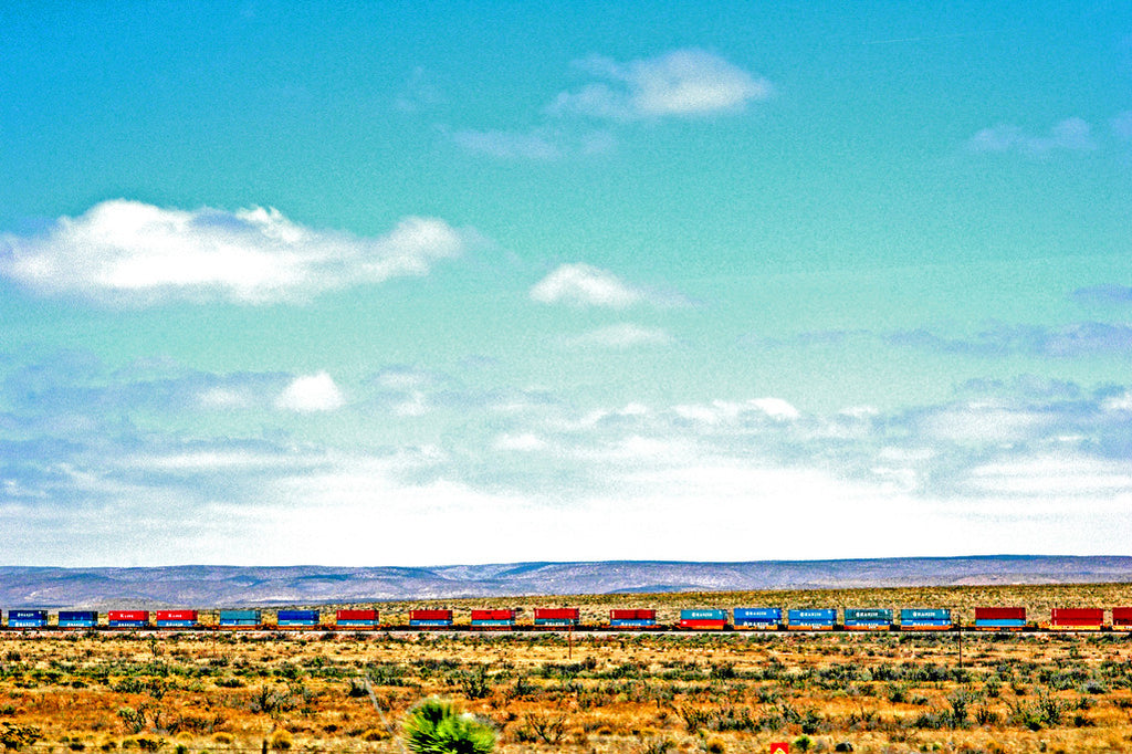 """West Texas Haul"" ~ A colorful freight train in the desert set against a blue sky. Photo by Ann Woodall"