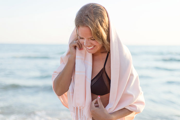 Pretty girl at the beach with pastel peach Turkish towel