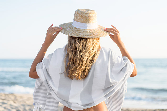Blonde girl at the beach with straw hat and grey striped Turkish towel