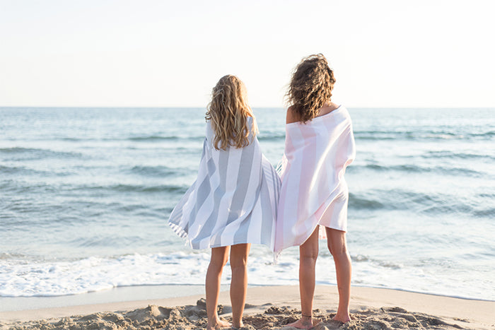 Friends at the beach with grey and pink striped Turkish towels
