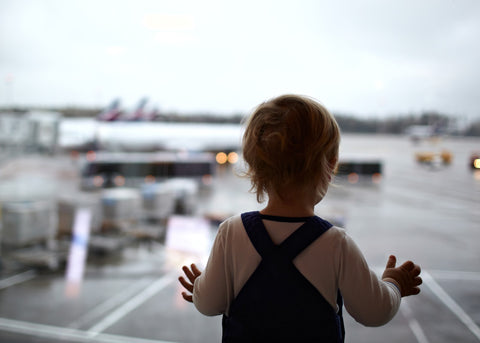 Traveling With Kids Tips - Small child looking at airplanes through window.