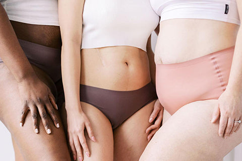 Close up of three women's torsos posed together in their underwear and hannahpads