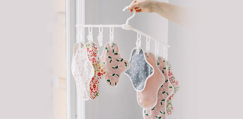 A cropped image of a hand holding a clothes hanger full of reusable menstrual pads