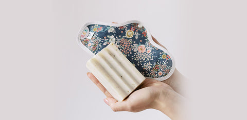 Close-up of hands holding probiotic laundry soap and a reusable menstrual pad