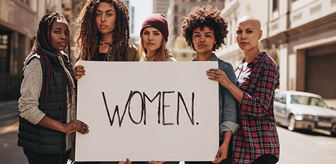 Five women holding a sign that says women