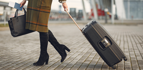 A woman dragging a travel bag while on a trip