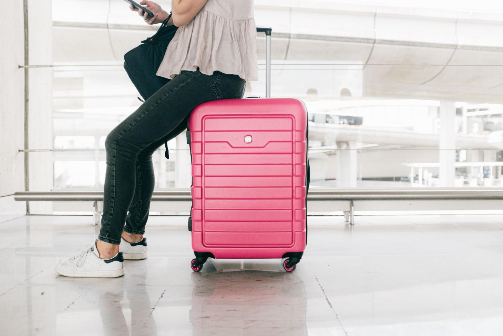 Cropped image of a woman sitting on a pink suitcase