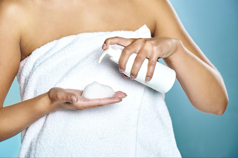 Cropped photo of a woman in a towel putting foam on her hands
