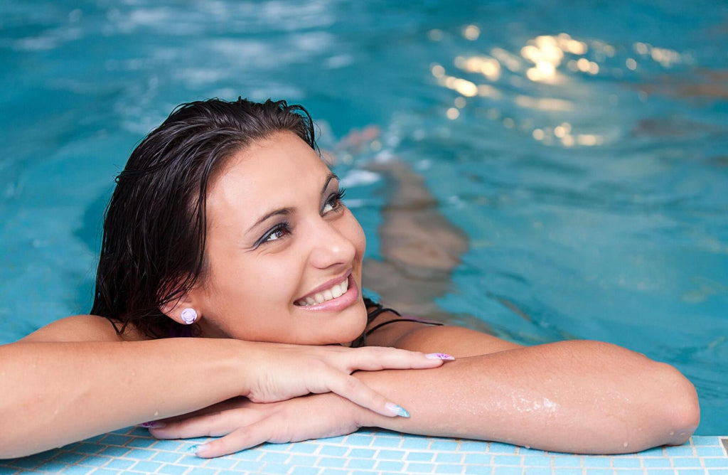 A smiling woman relaxing by the side of a pool