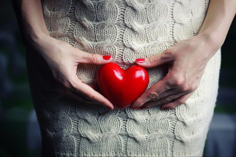 A cropped photo of a woman holding a small heart in front of the vaginal area