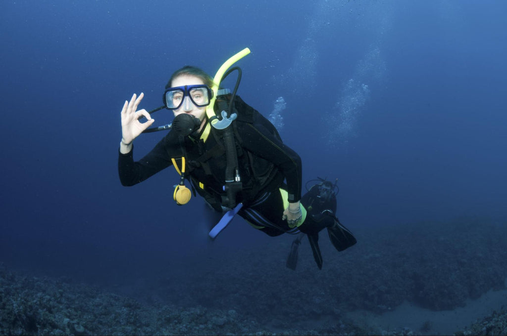 A female diver giving the OK sign