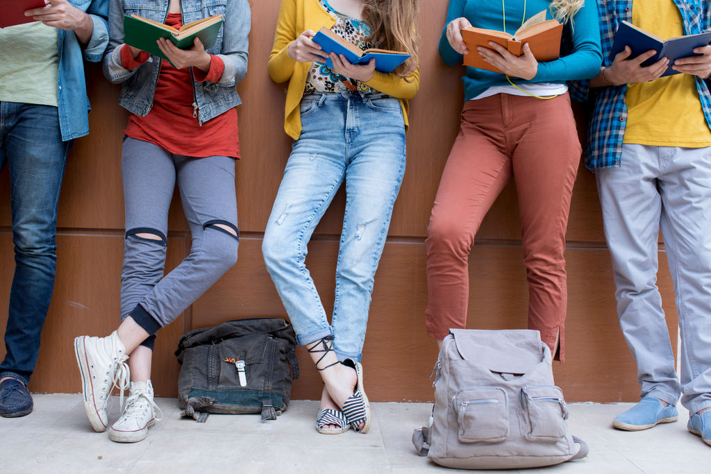 a group of teenage girls reading books