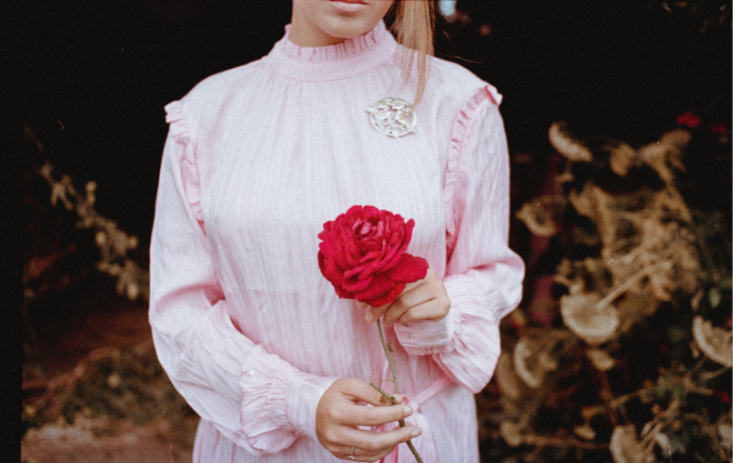 Cropped photo of a woman holding a red flower
