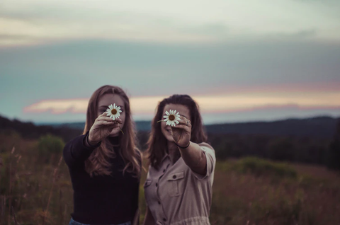 Two girls holding up a flower