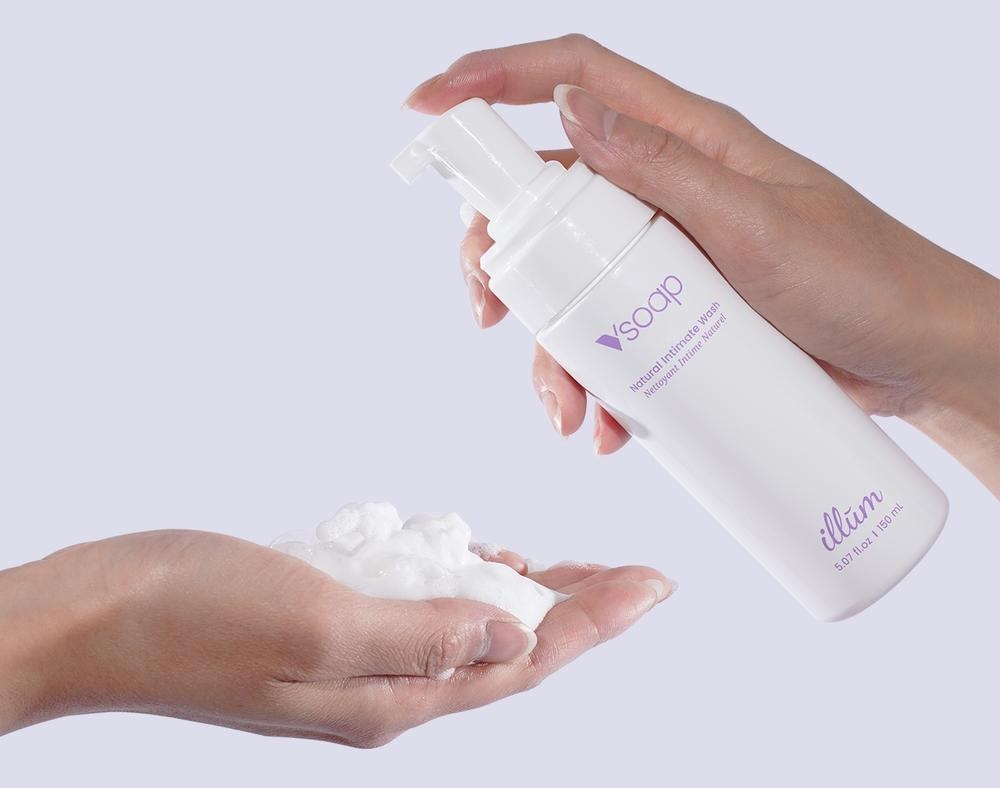 A woman holding a bottle of foamy illum intimate wash