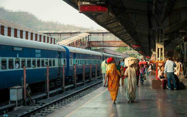 Train station in India with people on the platform coming and going.