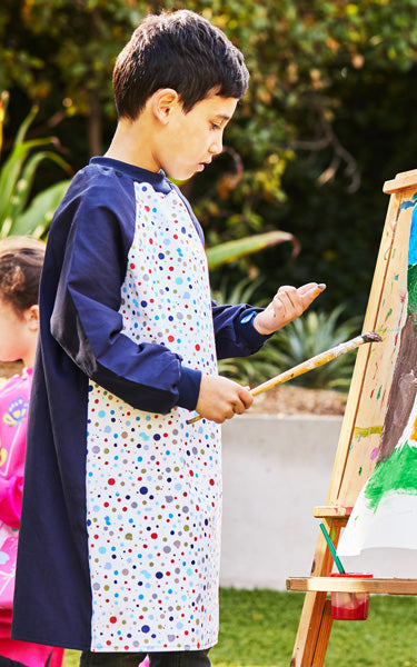 Boy painting in personalised splash art smock