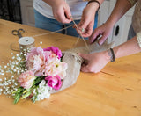 Tying a wrapped posy with twine