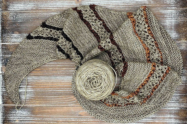 A partially knit Beeline shawl that is still on the knitting needles with a cake of Toasted Almond yarn