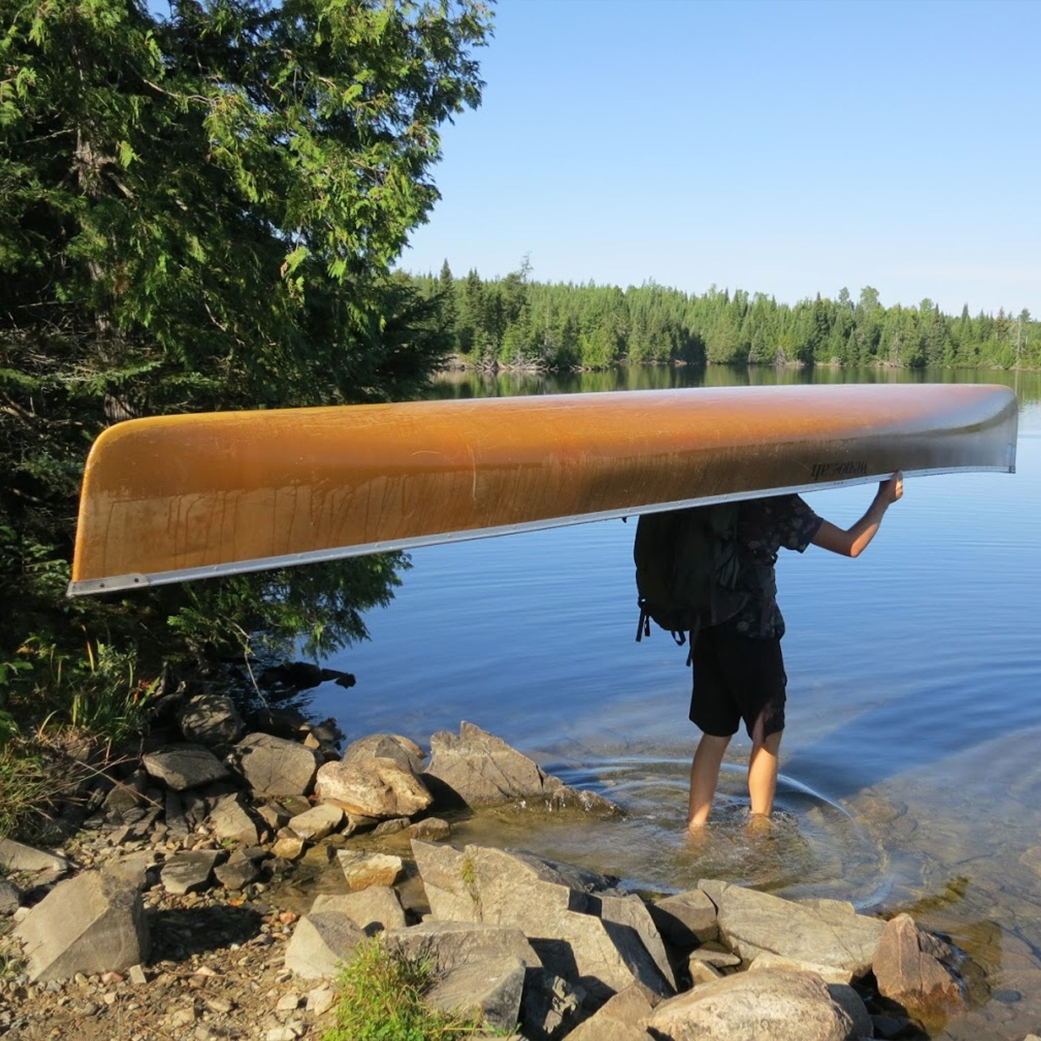 Jon Duff carrying canoe in mens tall clothing by Navas Lab Apparel