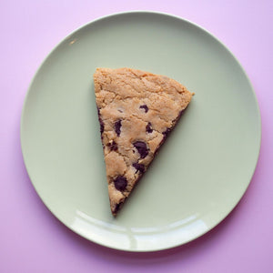 Slice of cookie pizza on plate giant chocolate chip vegan cookie