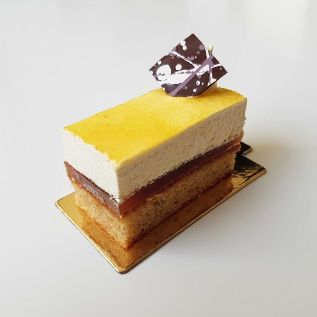 Passionfruit mango coconut gateau - layer of cake, then jelly, then cream, then glaze then chocolate decor sitting on top of a white background
