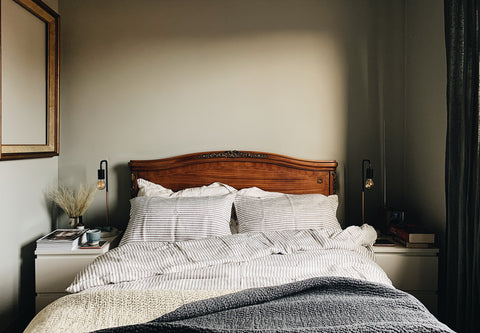 a vintage bed with grey stripe linen duvet cover and pillow cases