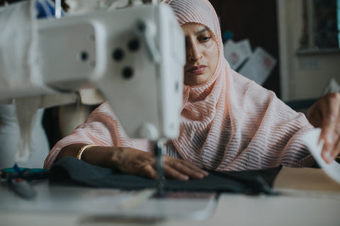 a woman in a pink headscarf sewing