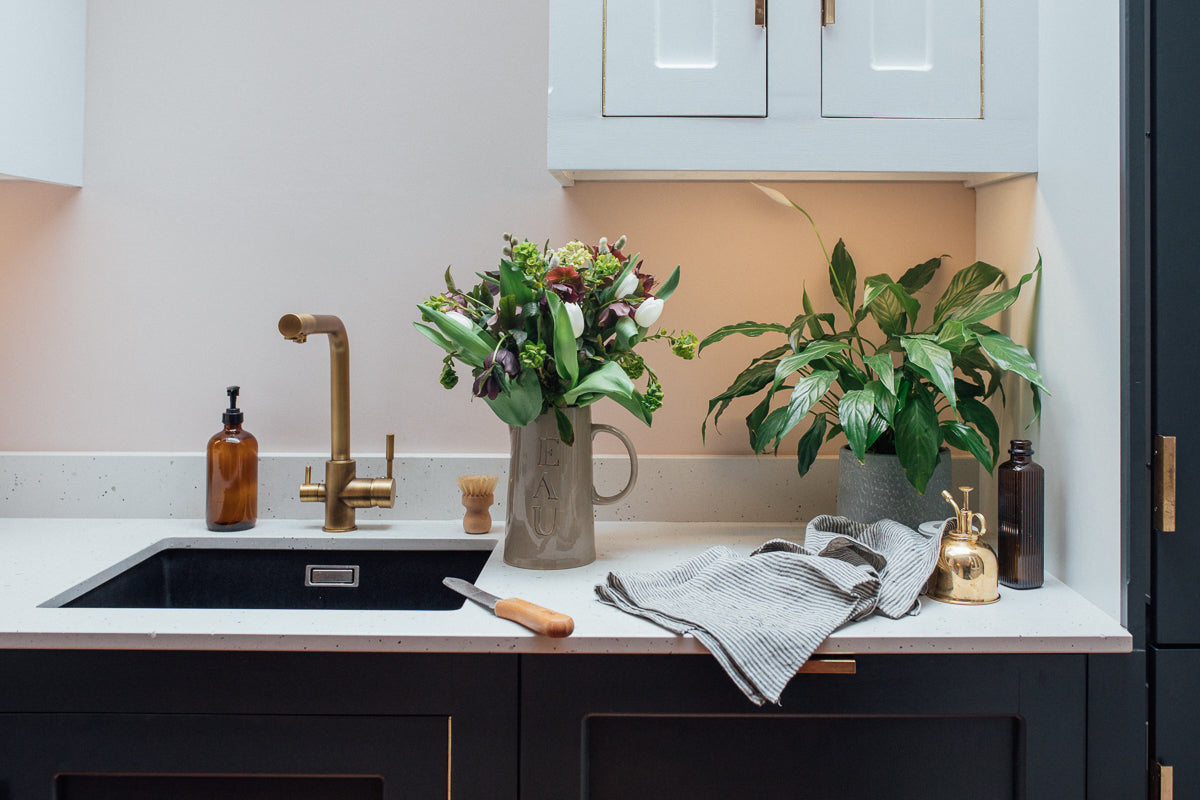 a kitchen sink with marble counters, plants and striped linen