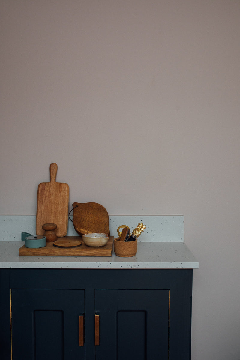 a blue kitchen unit with chopping boards and pots