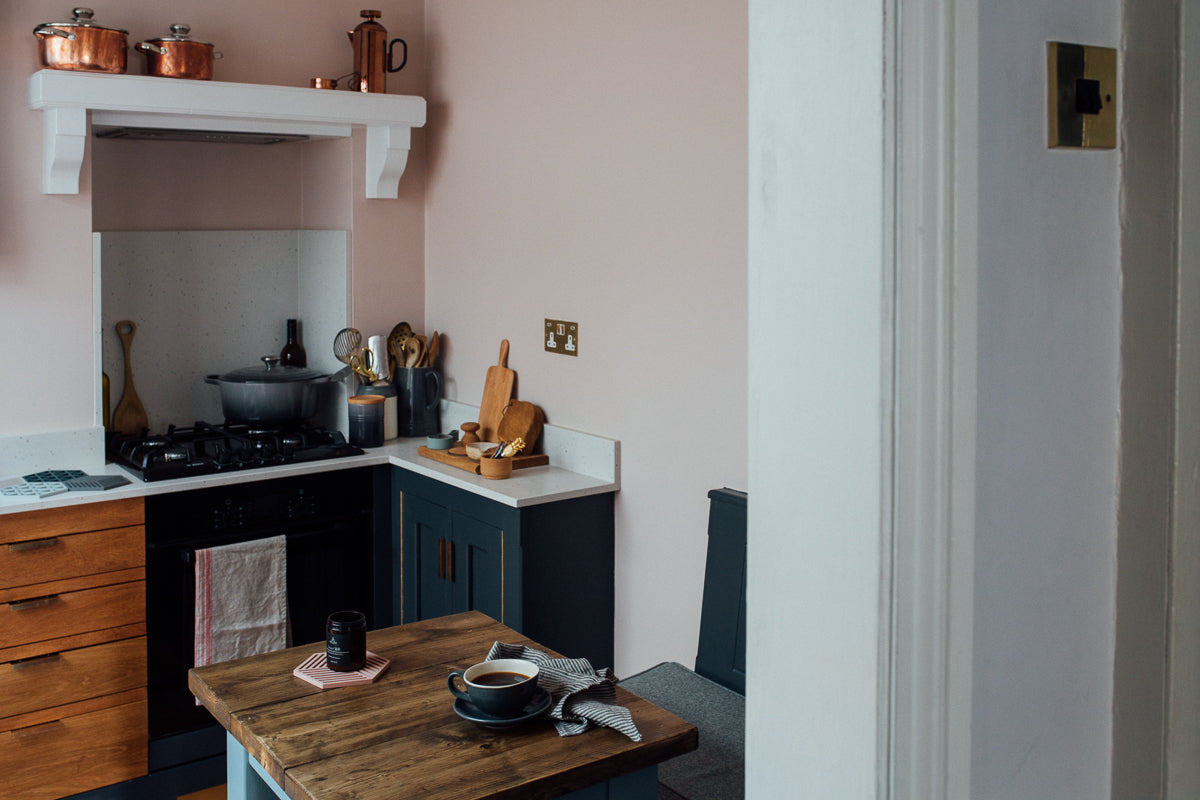 A kitchen corner with blue units and pink walls
