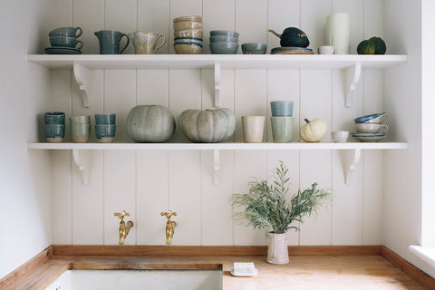 White shelves with blue and green pottery