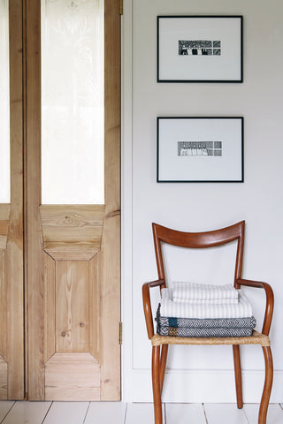 A chair next to a wooden door has striped linen and a blanket on it