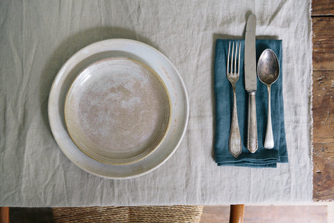 Cream stoneware dinner plates with a blue napkin