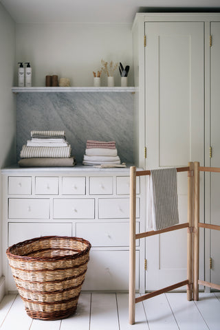 A wooden drying rack and a wicker basket in front of a white cupboard